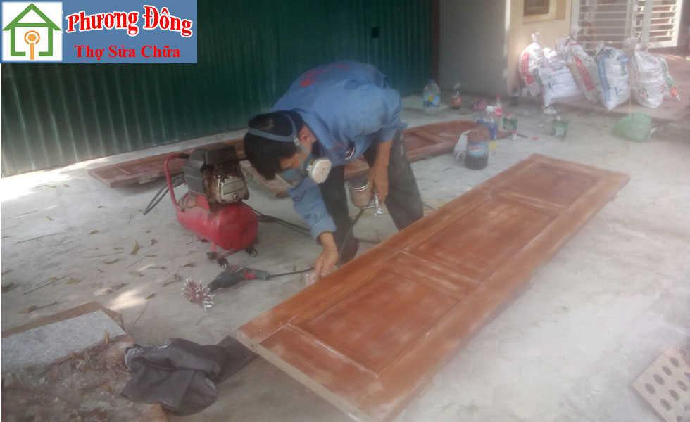 Thợ đang phun sơn cánh cửa gỗ