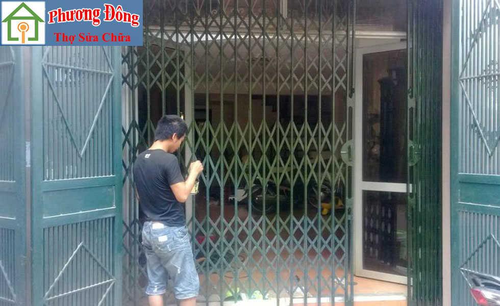Thợ đang sơn cửa xếp sắt tại nhà