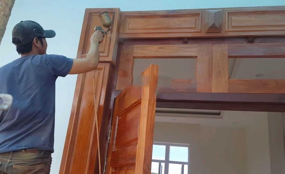 Thợ đang phun sơn khung cửa gỗ